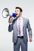 picture of shout  - Handsome businessman shouting in loudspeaker over gray background - JPG
