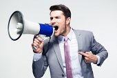 stock photo of shout  - Confident businessman shouting in loudspeaker over gray background - JPG