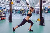 image of suspension  - Beautiful woman doing hard suspension training with fitness straps in a fitness center - JPG