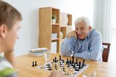 picture of senior men  - Senior man playing chess with a young man - JPG