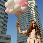 picture of high-rise  - Beautiful young girl holding colored balloons over high - JPG