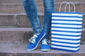 pic of street-walker  - Female feet in gumshoes near shopping bag on  stone stairs - JPG
