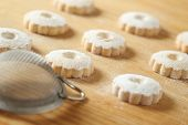 image of sprinkling  - Regular arrangement of italian canestrelli cookies on a raw wooden table with a strainer used to sprinkle icing sugar - JPG