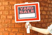 stock photo of yard sale  - Wooden Yard Sale sign in female hand on red brick wall background - JPG