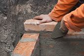 picture of trowel  - builder holding a red brick and trowel - JPG