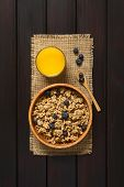 image of cereal bowl  - Dried berry and oatmeal breakfast cereal with fresh blueberries in wooden bowl with a glass of juice photographed overhead on dark wood with natural light - JPG