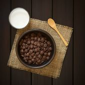 foto of cereal bowl  - Crispy chocolate corn flakes breakfast cereal in rustic bowl with a glass of milk and wooden spoon on the side photographed overhead on dark wood with natural light - JPG