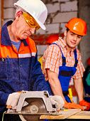 picture of millwright  - Happy group people  builder with circular saw - JPG