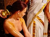image of panchakarma  - Young woman having pouring massage oil in ayurveda spa treatment - JPG