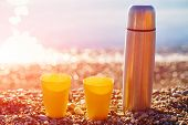 image of thermos  - two yellow cups and thermos on a sunny beach - JPG