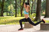 picture of squatting  - Smiling young woman doing squats in the park - JPG