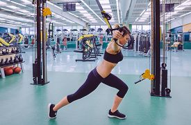 picture of suspension  - Beautiful woman doing hard suspension training with fitness straps in a fitness center - JPG