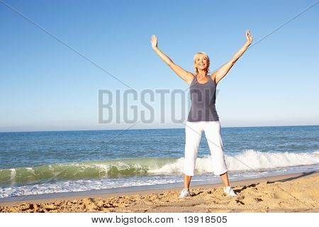 Постер, плакат: Старший женщина в фитнес одежда растяжения на пляже, холст на подрамнике