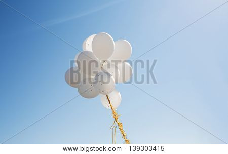holidays, birthday, party and decoration concept - close up of inflated white helium balloons in blu