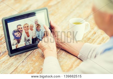 technology, age, memories and people concept - happy senior woman with tablet pc computer viewing fa