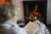image of reading book  - Senior Woman Reading Book By Fire At Home - JPG