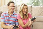 Young Couple Playing Computer Game On Sofa At Home poster