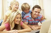 pic of happy family  - Family Using Laptop At Home Together - JPG