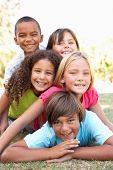 image of mixed race  - Group Of Children Piled Up In Park - JPG