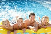 picture of swimming pool family  - Young family having fun together in pool - JPG