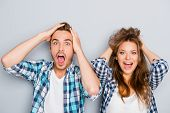 Portrait Of Surprised Man And Woman Screaming And Touching Hair poster