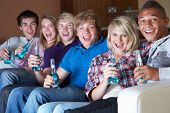 foto of underage  - Group Of Teenage Friends Sitting On Sofa At Home Watching Drinking Alcohol - JPG