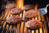 Juicy beef hamburger patties sizzling over hot flames on the barbecue poster