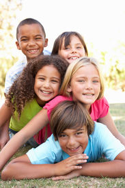 stock photo of children group  - Group Of Children Piled Up In Park - JPG
