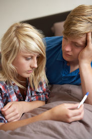 stock photo of underage  - Two Teenage Girls Lying On Bed Looking At Pregnancy Testing Kit - JPG