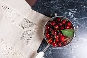 Fresh Organic Sweet Cherry And Big Green Leaf In Steel Colander On Dark Marble Background. poster