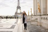 Nice Woman In Grey Coat Standing On Trocadero Square Near Gilded Statues And Eiffel Tower In Paris.  poster