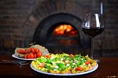 Tasty Pizza And Glass With Red Wine In A Traditional Restaurant With A Fire Stone Stove. Background  poster