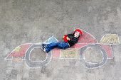 Adorable Little Kid Boy Drawing With Colorful Chalks Race Car Picture On Asphalt. Cute Toddler And P poster