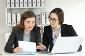 Two Executives Working Together Talking About Documents At Workplace poster