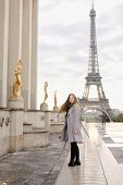 Young Pretty Woman In Grey Coat Standing On Trocadero Square Near Gilded Statues And Eiffel Tower In poster