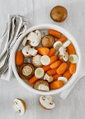 Raw Carrots, Mushrooms And Leeks In Saucepan For Steamed On White Wooden Table, Top View. Steam Cook poster