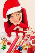 pic of sad christmas  - Sad christmas santa woman wrapping gifts depressed and bored wearing santa hat - JPG