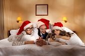 stock photo of promiscuous  - Manager with two his subordinates look out under cover in bed on New Year - JPG