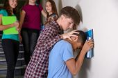 Teenager bullying African American boy indoors poster