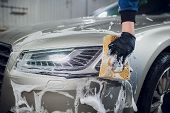 Outdoor Car Wash With Yellow Sponge. Beautiful Man Washes The Car poster