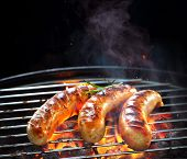 Grilled sausages on grill with smoke and flame on dark background poster