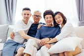 Asian Family With Adult Children And Senior Parents Relaxing On A Sofa At Home Together poster