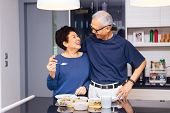Senior Asian Couple Grandparents Cooking Together While Woman Is Feeding Food To Man At The Kitchen. poster