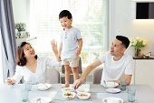 Asian Family Watching Their Kid As He Is Determined And Proud To Finally Stand On The Dining Table poster