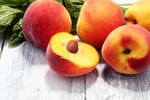 A Group Of Ripe Peaches On Table poster