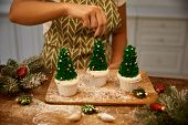 Cropped View Of Confectioner Sprinkling Decor On Christmas Tree Cupcakes Beside Baubles And Spruce B poster