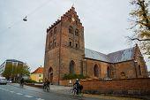 Odense, Denmark: Beautiful Traditional Brick Church On The Street. Odense, Funen Island, Denmark poster
