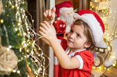 Little Girl In Christmas Dress Decorating Christmas Tree With Baubles. Christmas Kid Decorating Chri poster