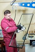 foto of suction  - glazier worker with suction cup holding glass at double glazing window manufacture - JPG