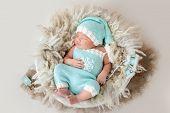 Beautiful newborn sleeping in comfortable basket poster